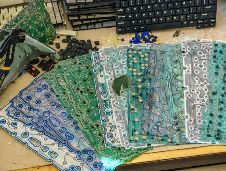 Behind the old laptop keyboard keys are some great circuitry patterns.
